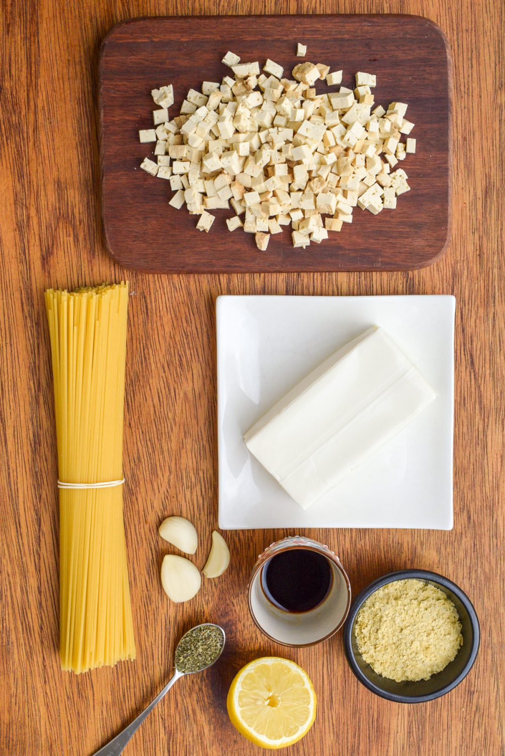 Ingredients for the vegan carbonara - a block of silken tofu, diced smoked tofu, a bunch of spaghetti, garlic cloves, herbs, half a lemon, soy sauce and nutritional yeast.