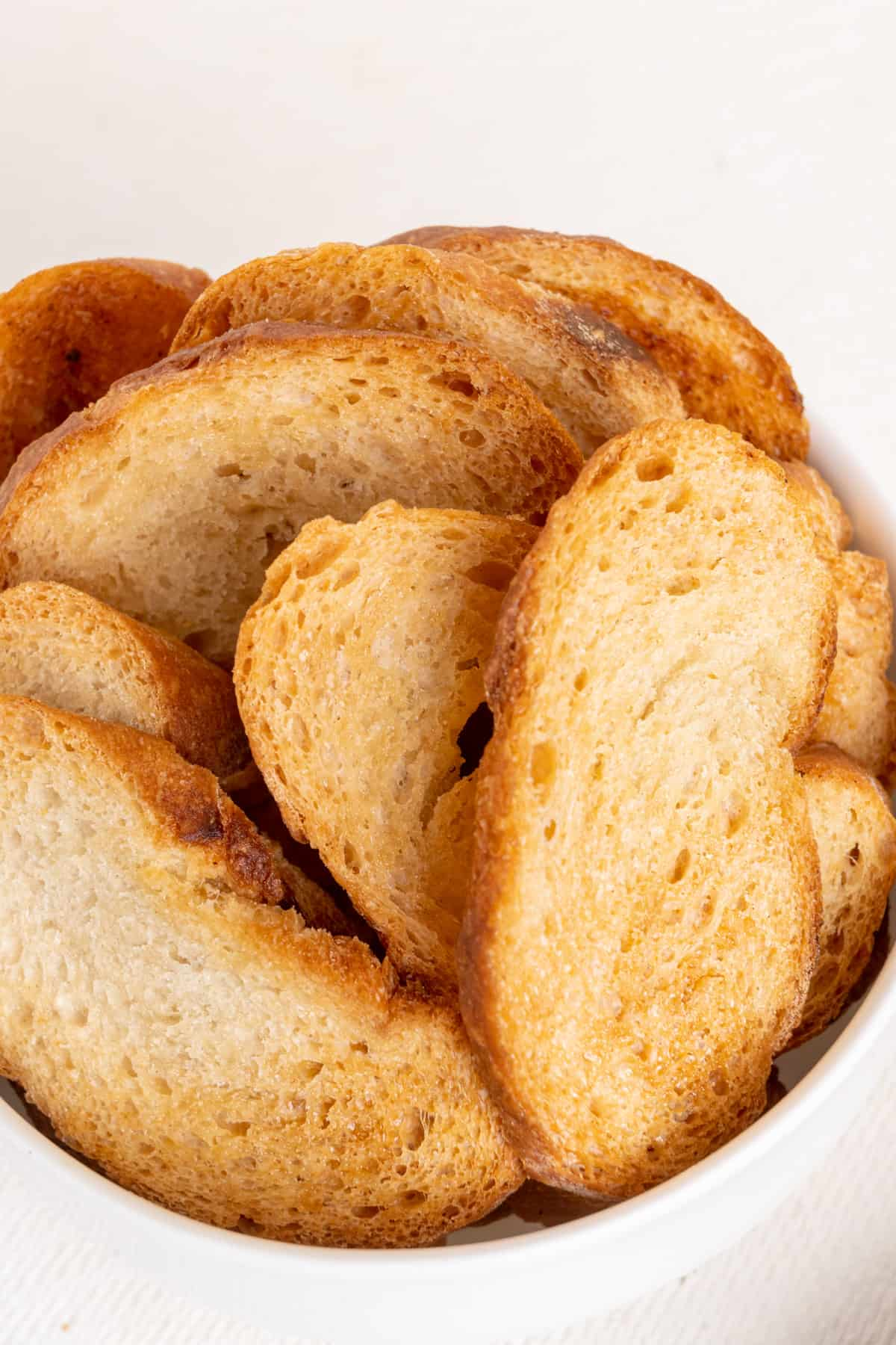 A bowl of thin slices of baguette, baked golden brown and crispy.