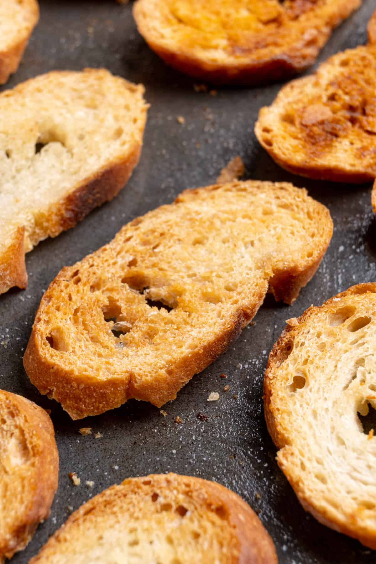 A close up image of crostini. The slices of bread have been baked until golden brown and very crispy.