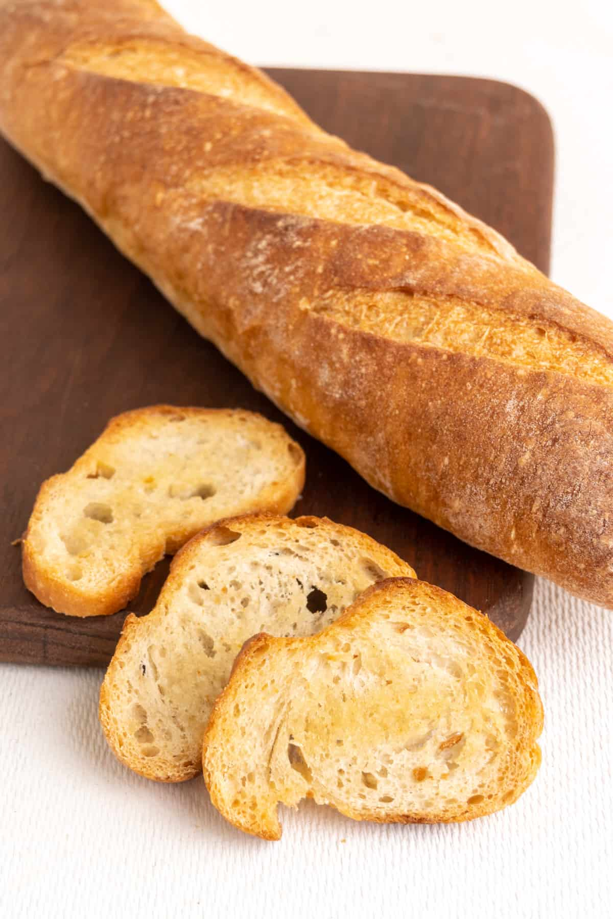 Three crostini, which are crispy baked thin slices of bread, next to a baguette on a wooden board.