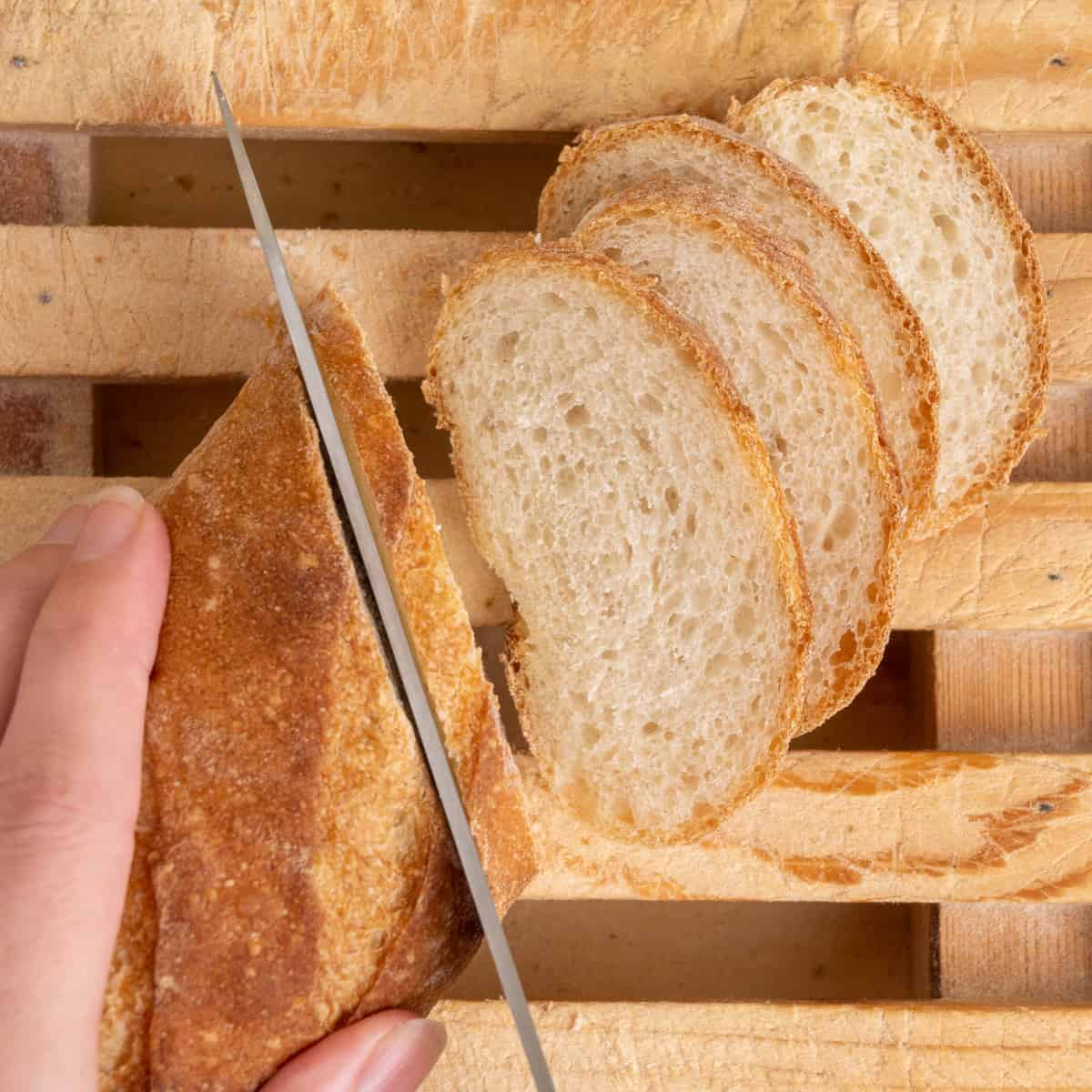 A baguette is sliced into thin diagonal slices.