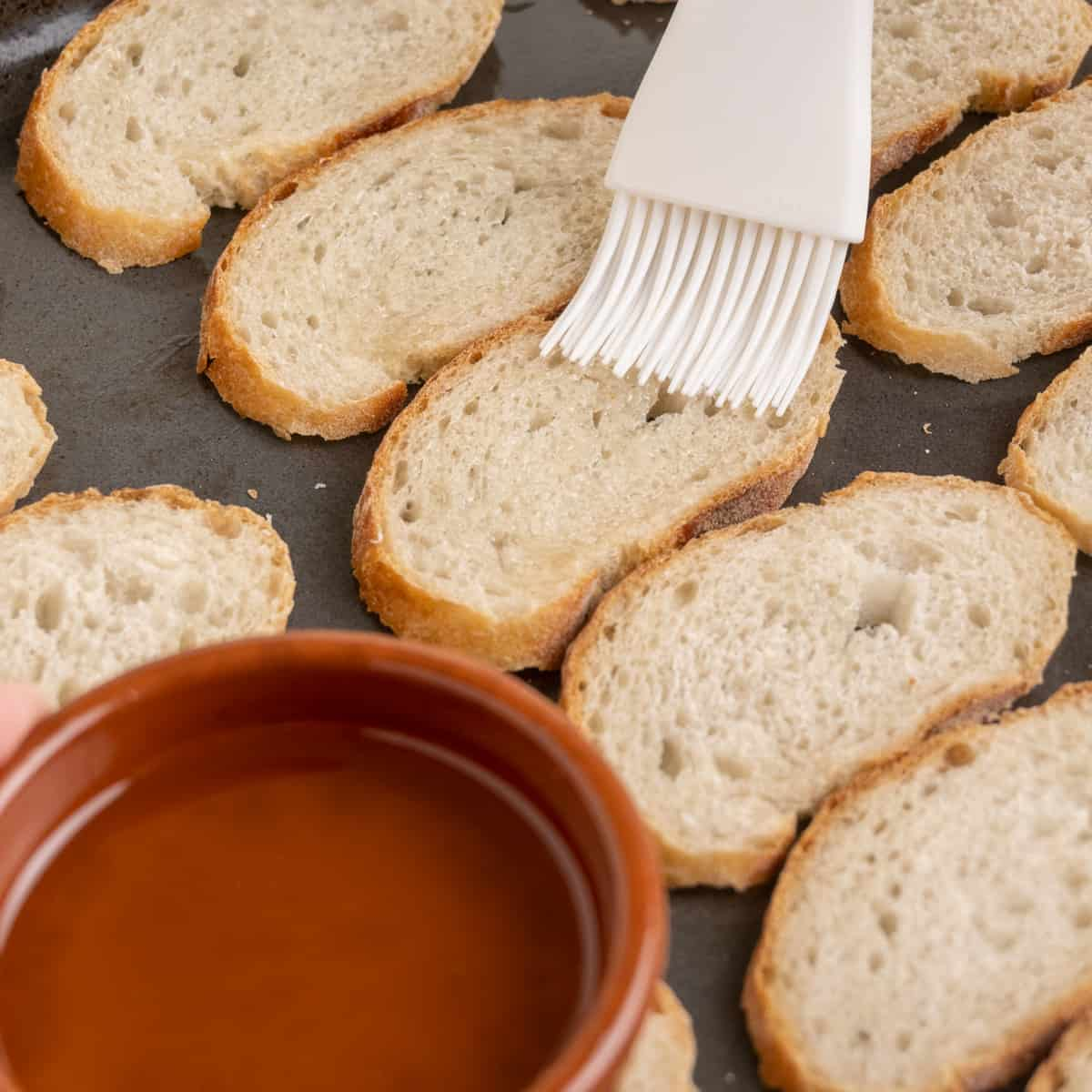 The thin slices of bread spread out on a baking tray are brushed with olive oil.