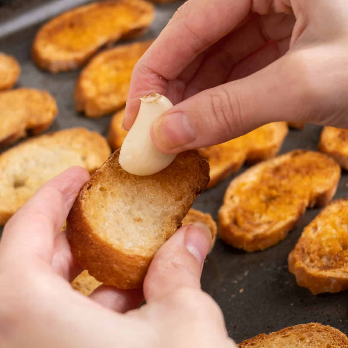 A fresh garlic clove is rubbed across a crostini to flavour it.