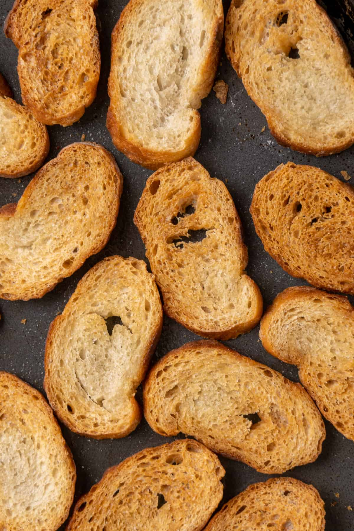 Small oval golden brown re-baked slices of bread on a baking tray.