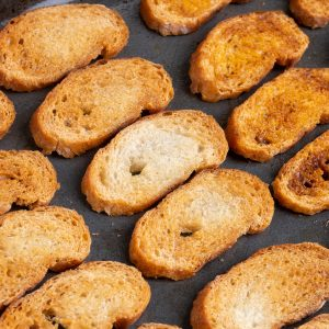 Crostini on the tray after baking. They are golden brown and appear crispy.
