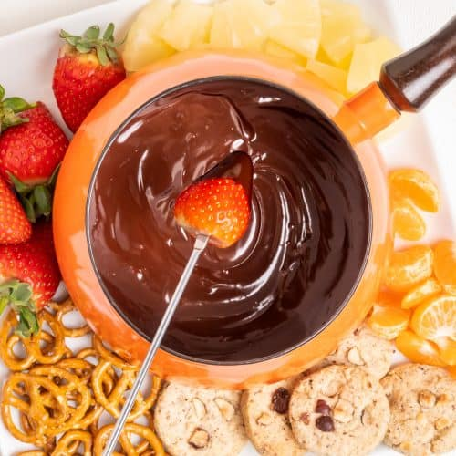 Dipping a strawberry into a chocolate fondue in a pan, surrounded by cookies and fruit.