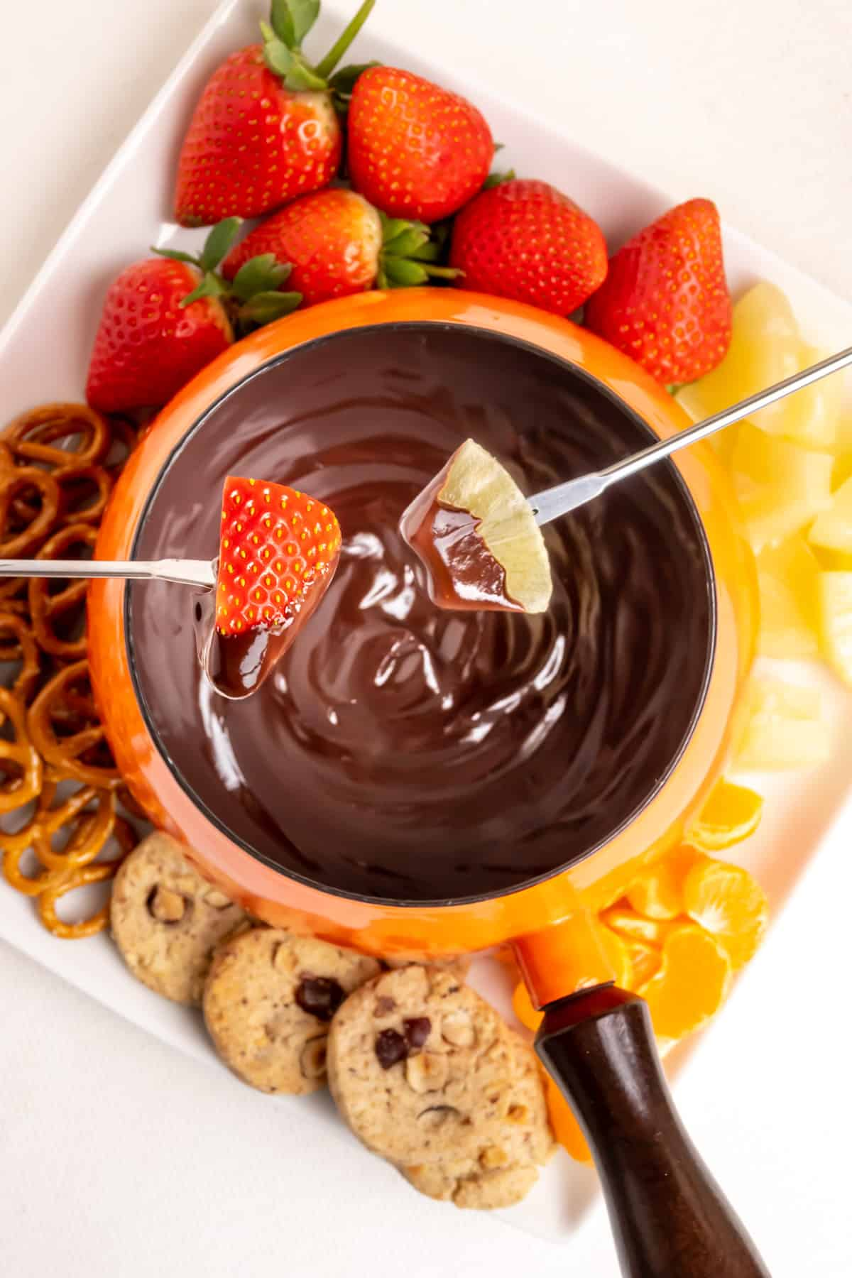 Dipping strawberry and pineapple into a pan of chocolate fondue.
