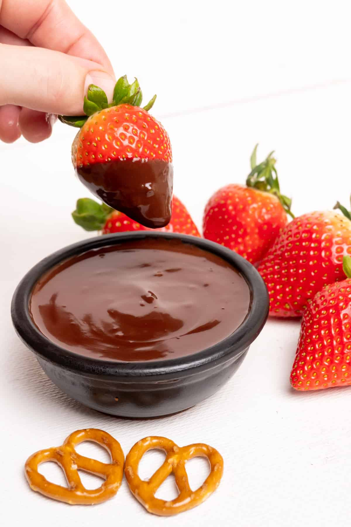 A hand holds a strawberry covered in dark chocolate fondue.