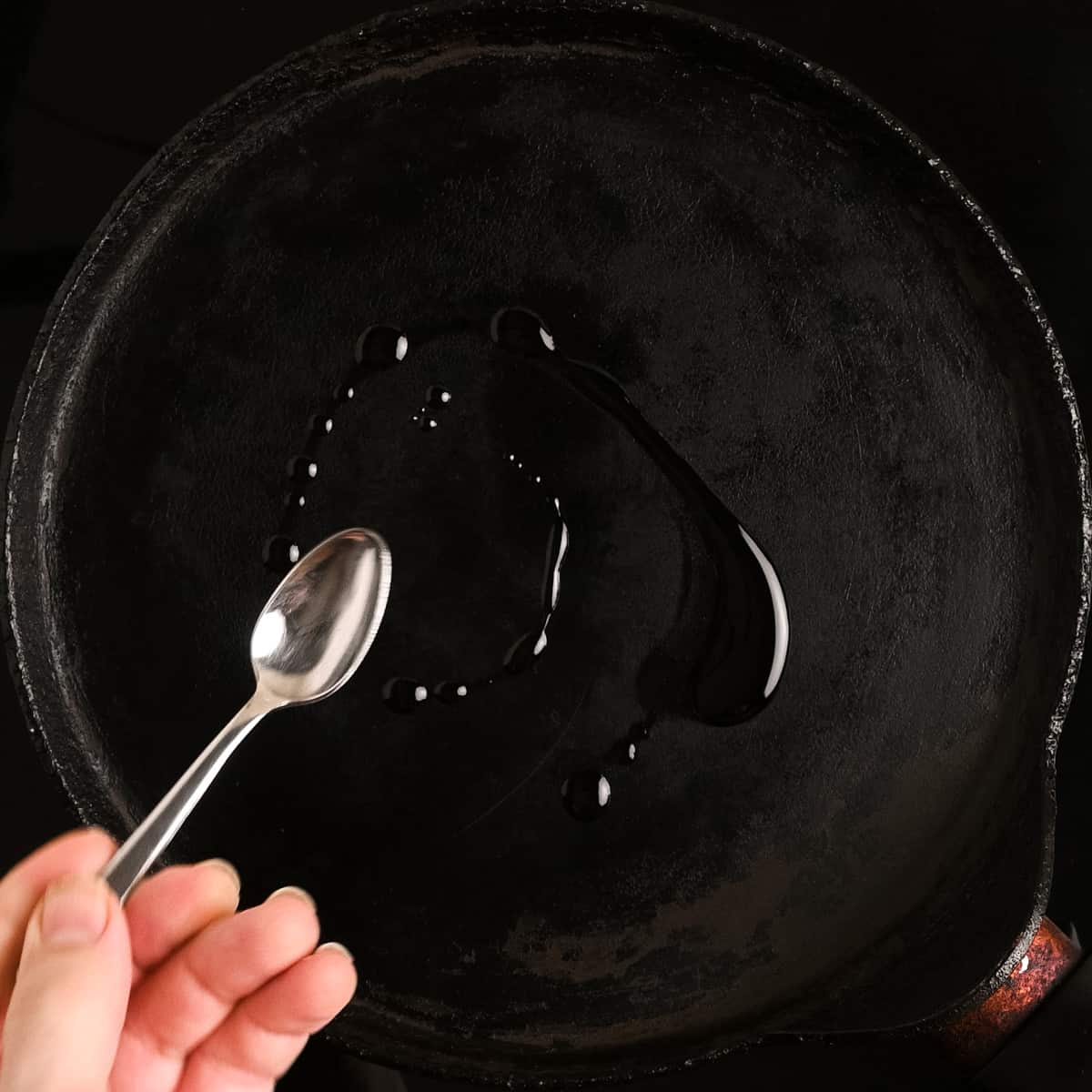 Heating up a crepe pan with a small spoonful of oil.