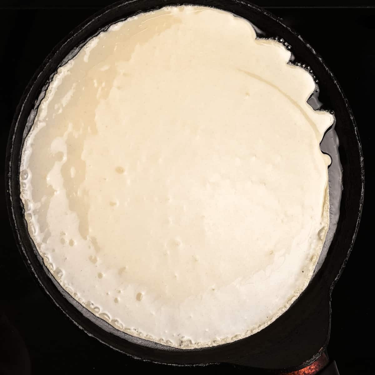 Tilting the pancake pan to spread out the batter.