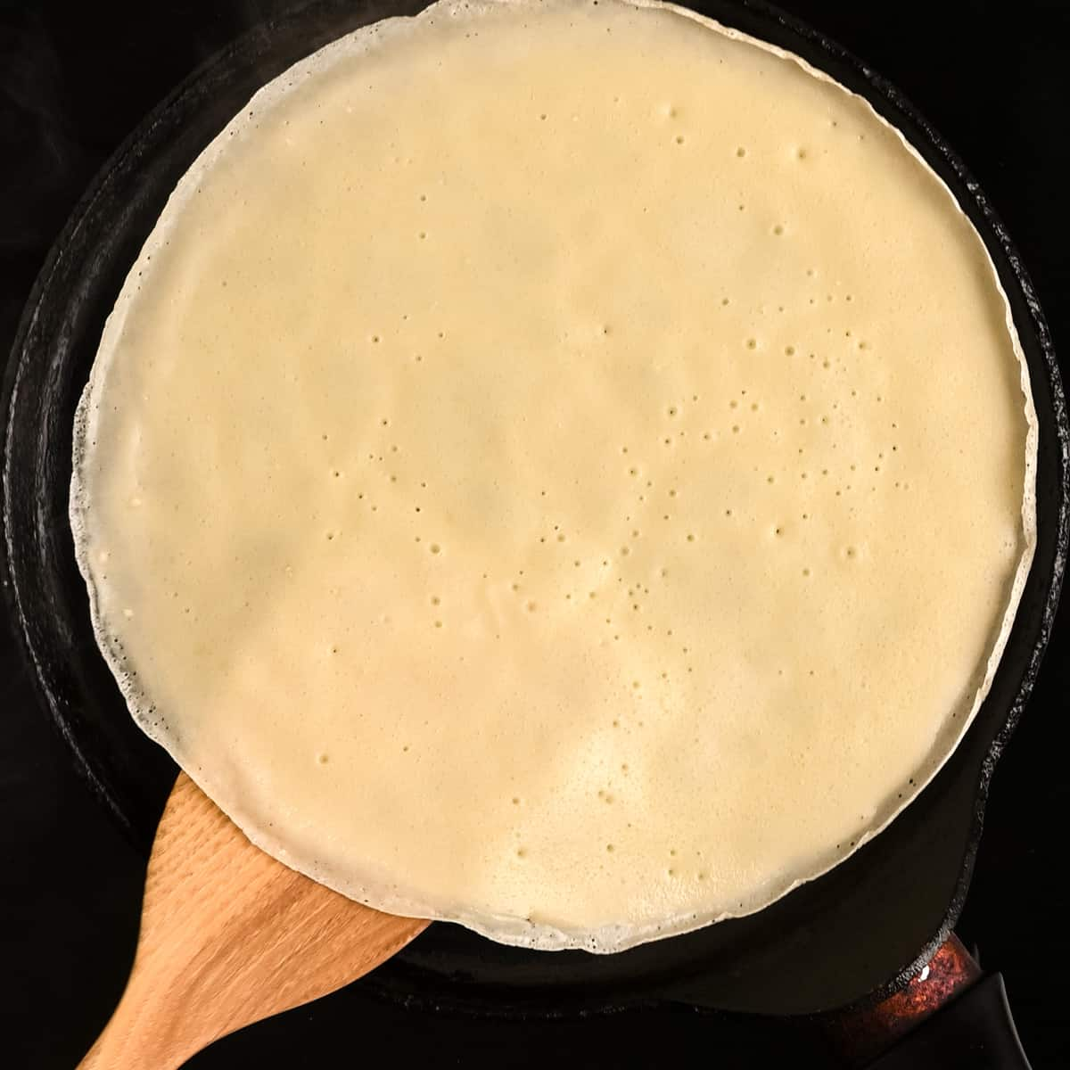 A spatula about to flip over a vegan crepe.