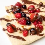Three folded crepes on a plate topped with berries and chocolate sauce.