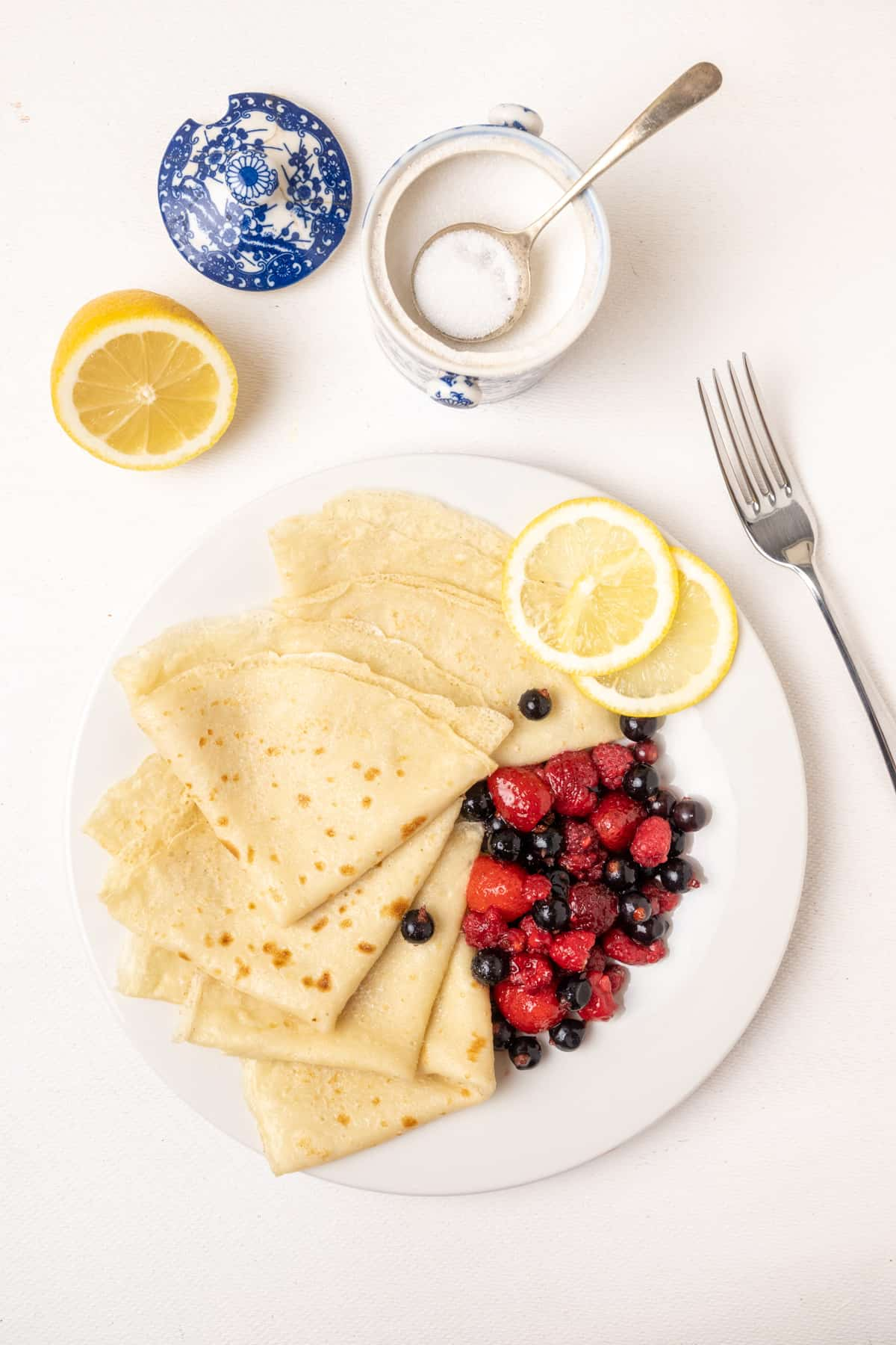 A plate of thin vegan pancakes with lemon and a sugar bowl next to it.