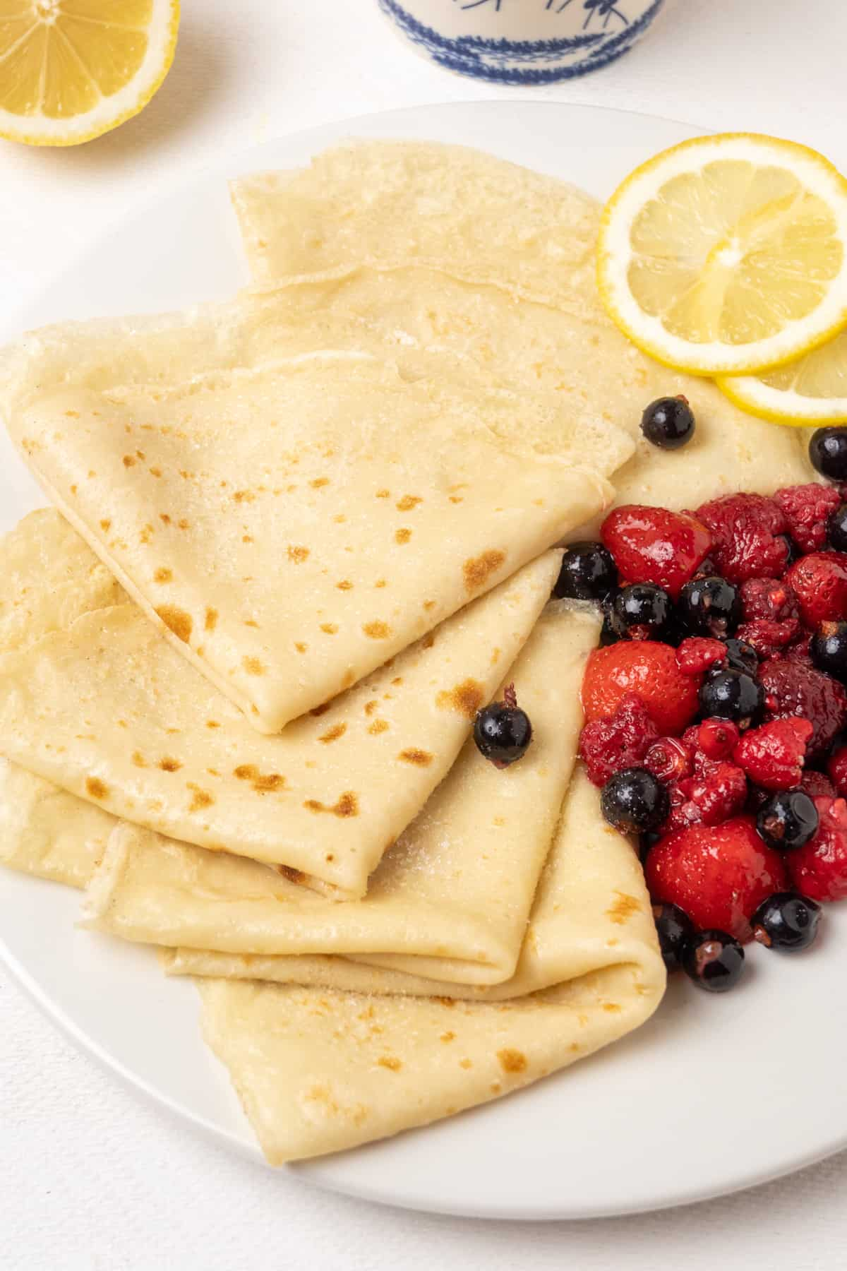 Folded vegan crepes on a plate with fruit and lemon.