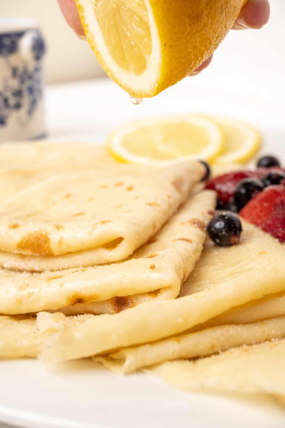 Squeezing lemon onto a pile of thin pancakes.