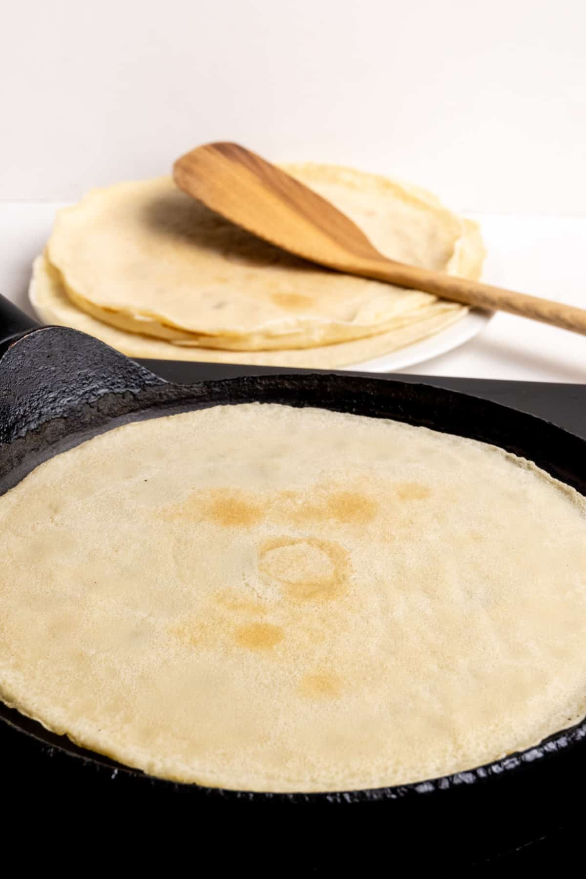Cooking a crepe in a pan, with a stack of cooked crepes and a wooden spatula in the background.