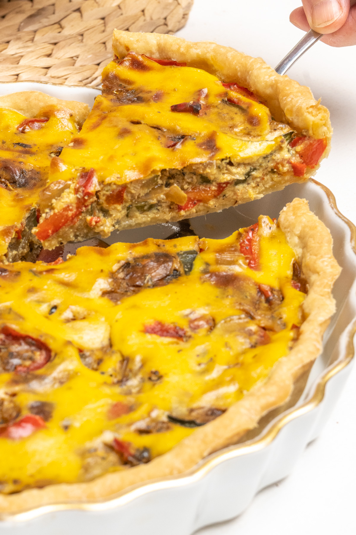 A metal slice lifts a piece of quiche.