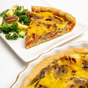A slice of herby vegetable filled vegan quiche on a white plate with kale salad on the side.