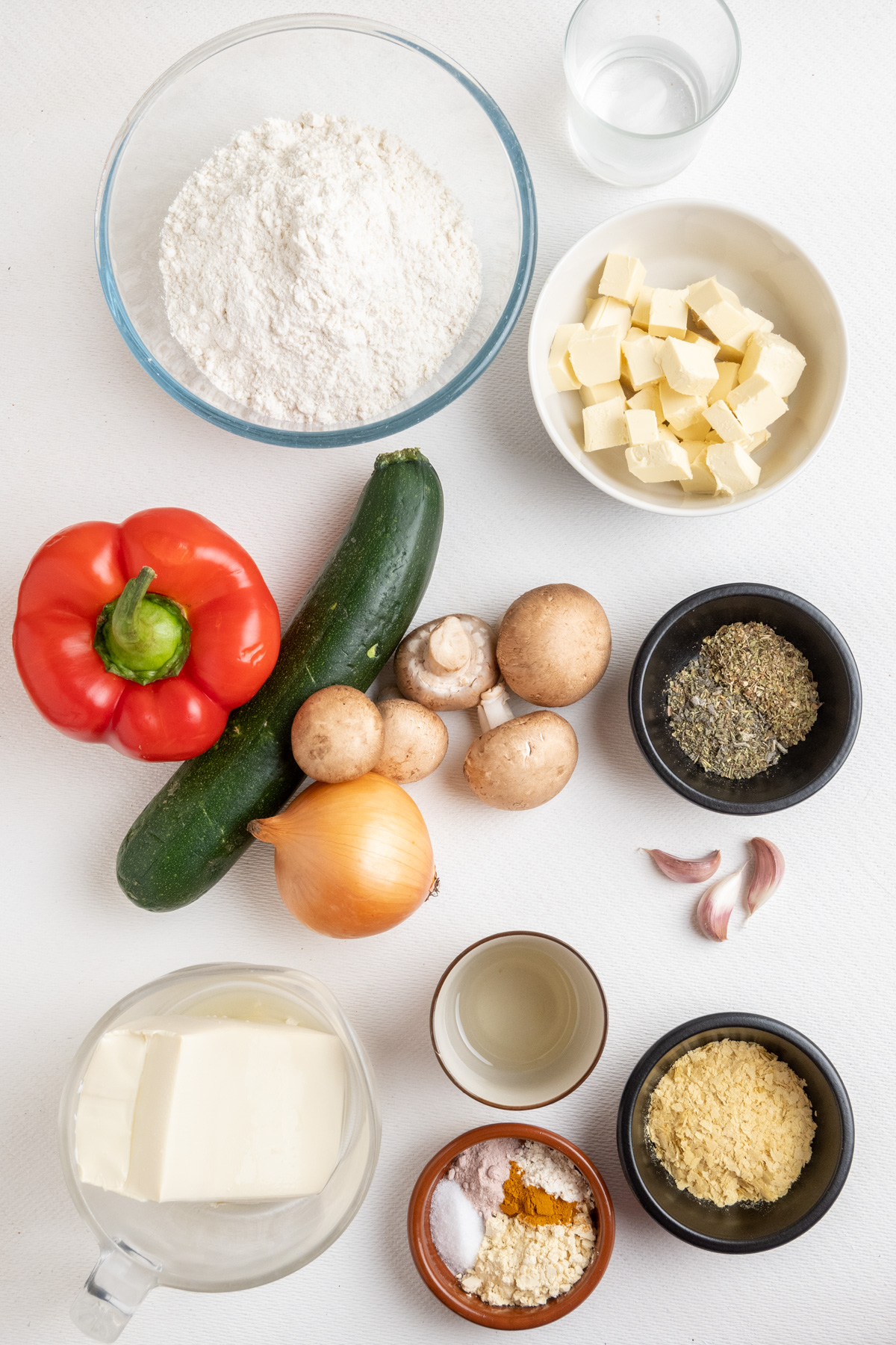 Ingredients for vegan vegetable quiche on a white surface.