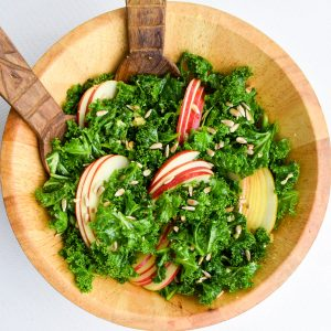 A wooden bowl of massaged kale salad with apples slices and sunflower seeds on top.