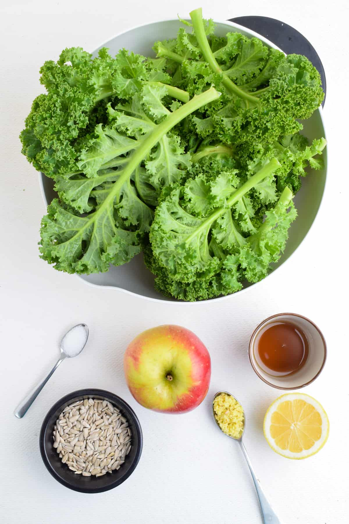 A bowl of curly kale leaves, alongside the other ingredients for the salad.