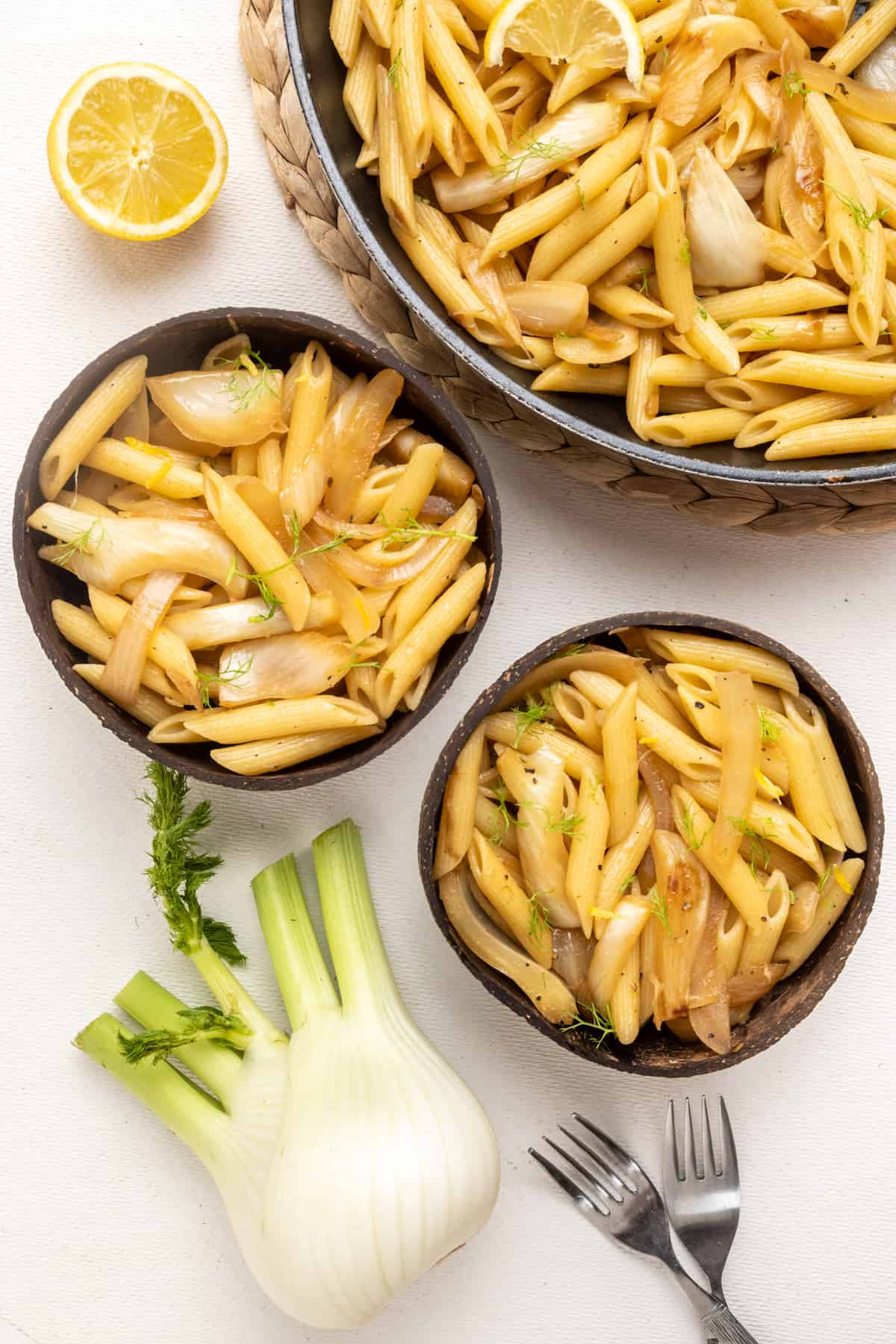 A top down shot of a large frying pan full of fennel pasta and two portions served in coconut bowls. Also in the picture, a whole fennel bulb, half lemon, and two forks.