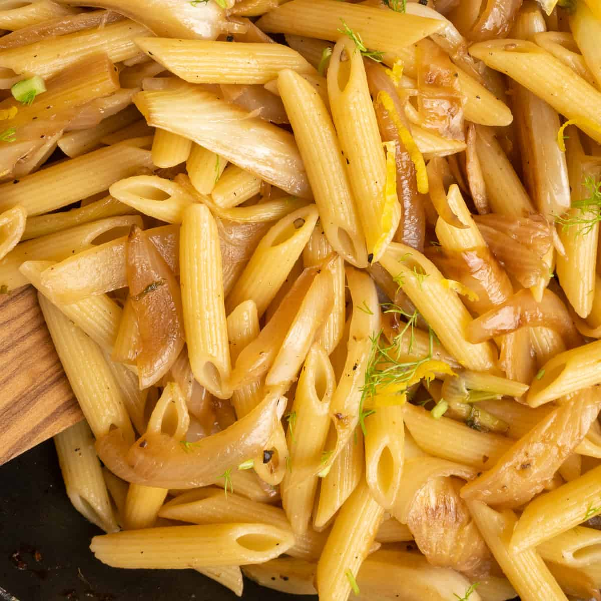 The pasta is stirred into the seasoned fried fennel and onion. The dish is finished by adding the chopped up fresh fennel fronds and some lemon peel.