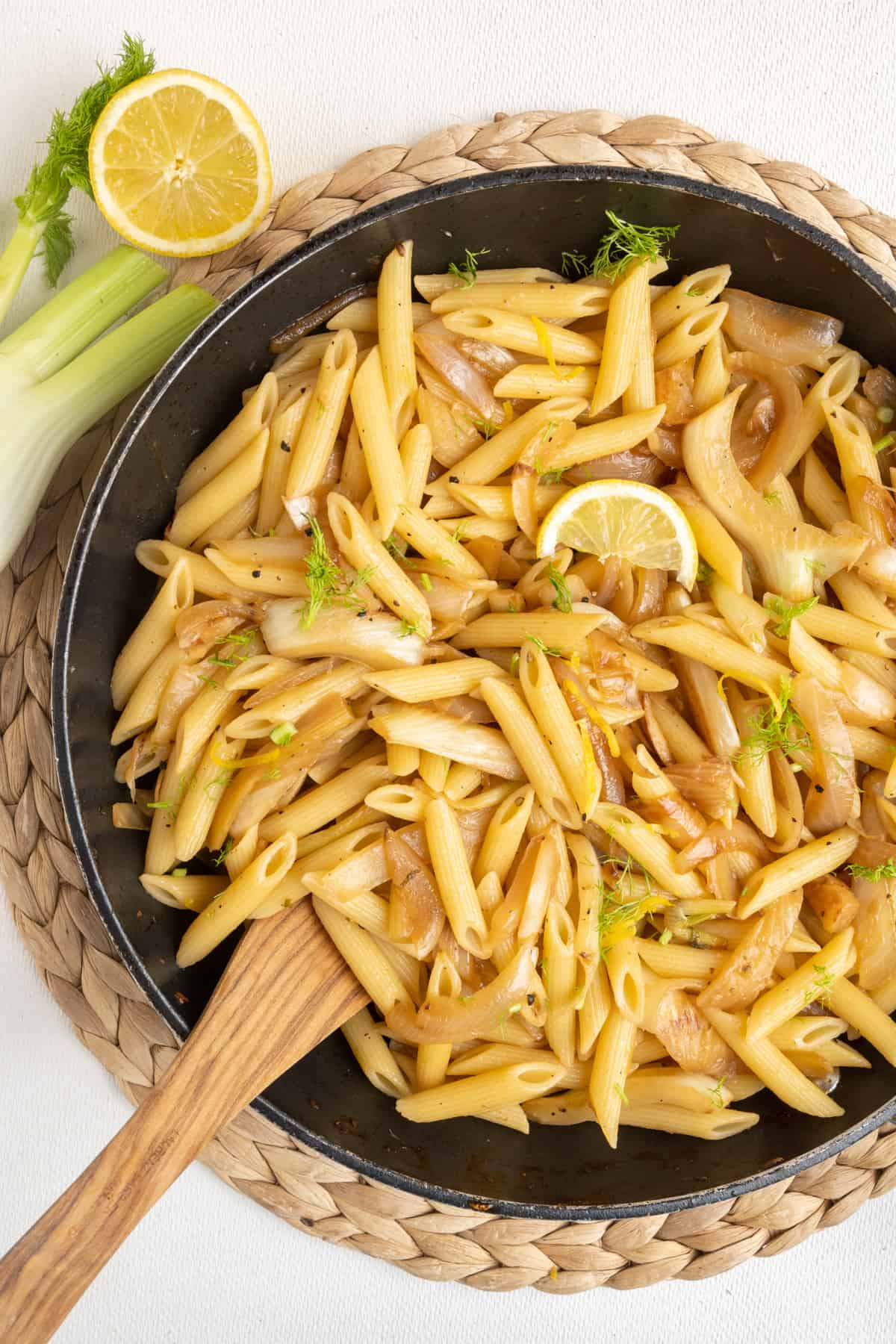 A top down view of a frying pan full of the finished fennel pasta. Around it a bulb of fennel and a half lemon.