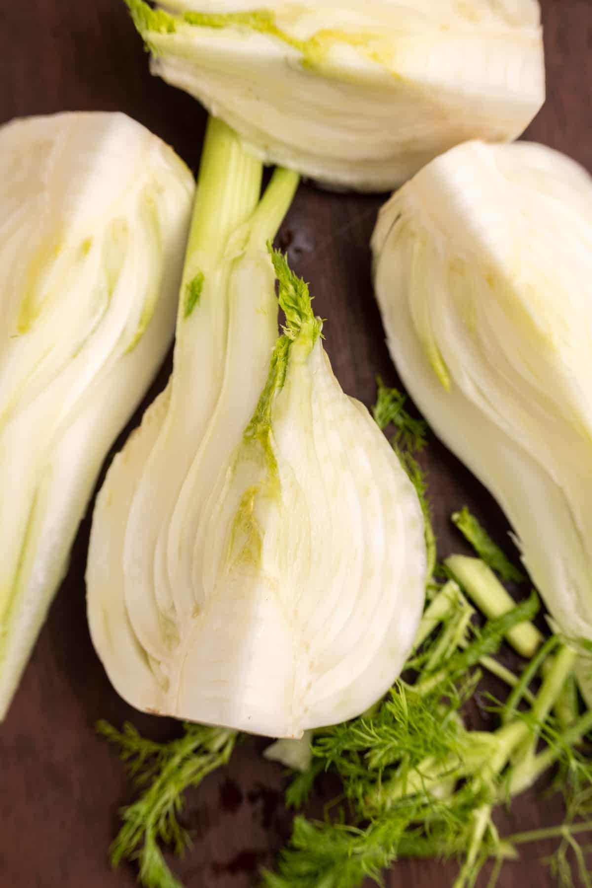A bulb of fennel cut into quarters. The quarter bulbs are sitting on a wooden board, and the green fronds have been chopped off and set aside.