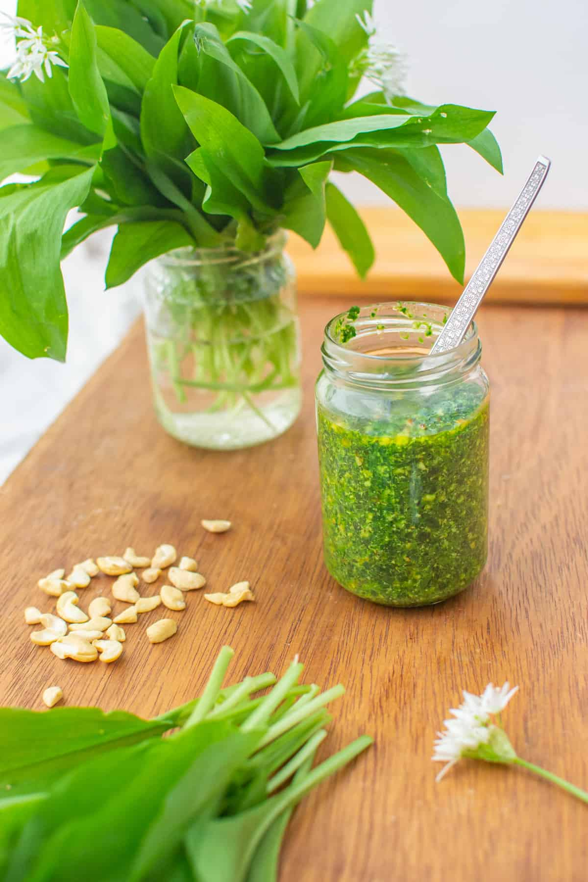A jar of pesto with a spoon in it, standing in between some wild garlic in a jar with water and some leaves on the table. Some cashew nuts are scattered besides the jar.