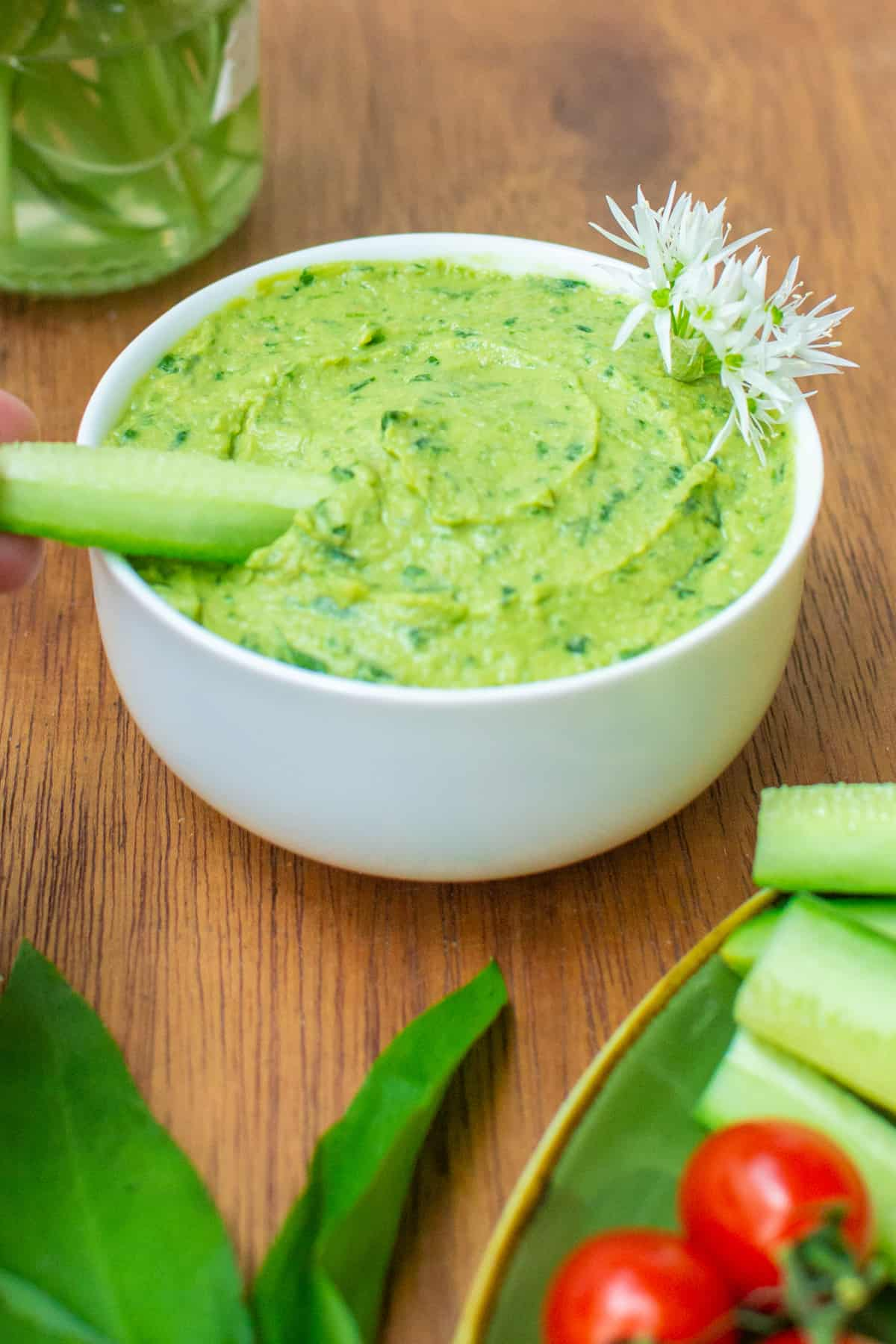 Dipping a stick of cucumber in the green hummus.