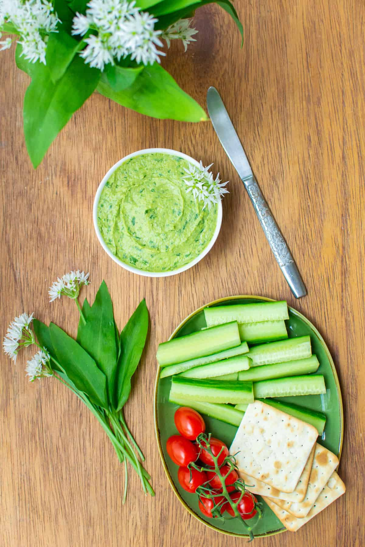 A bowl of green hummus decorated with wild garlic flowers, next to a plate of crudités and crackers.