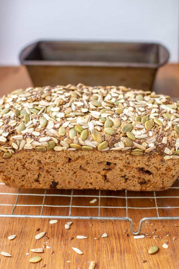 A rectangular loaf of rye bread topped with oats, pumpkin and sunflower seeds.