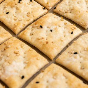 Diamond shaped sourdough crackers on a baking tray.