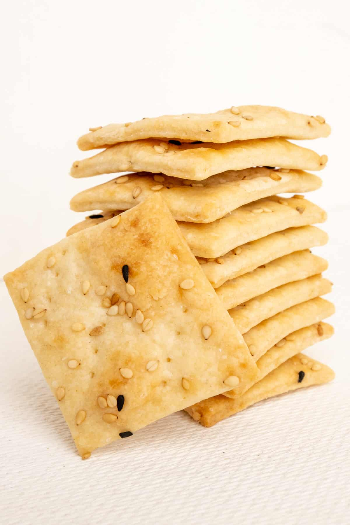 A stack of small sourdough crackers topped with sesame and nigella seeds.
