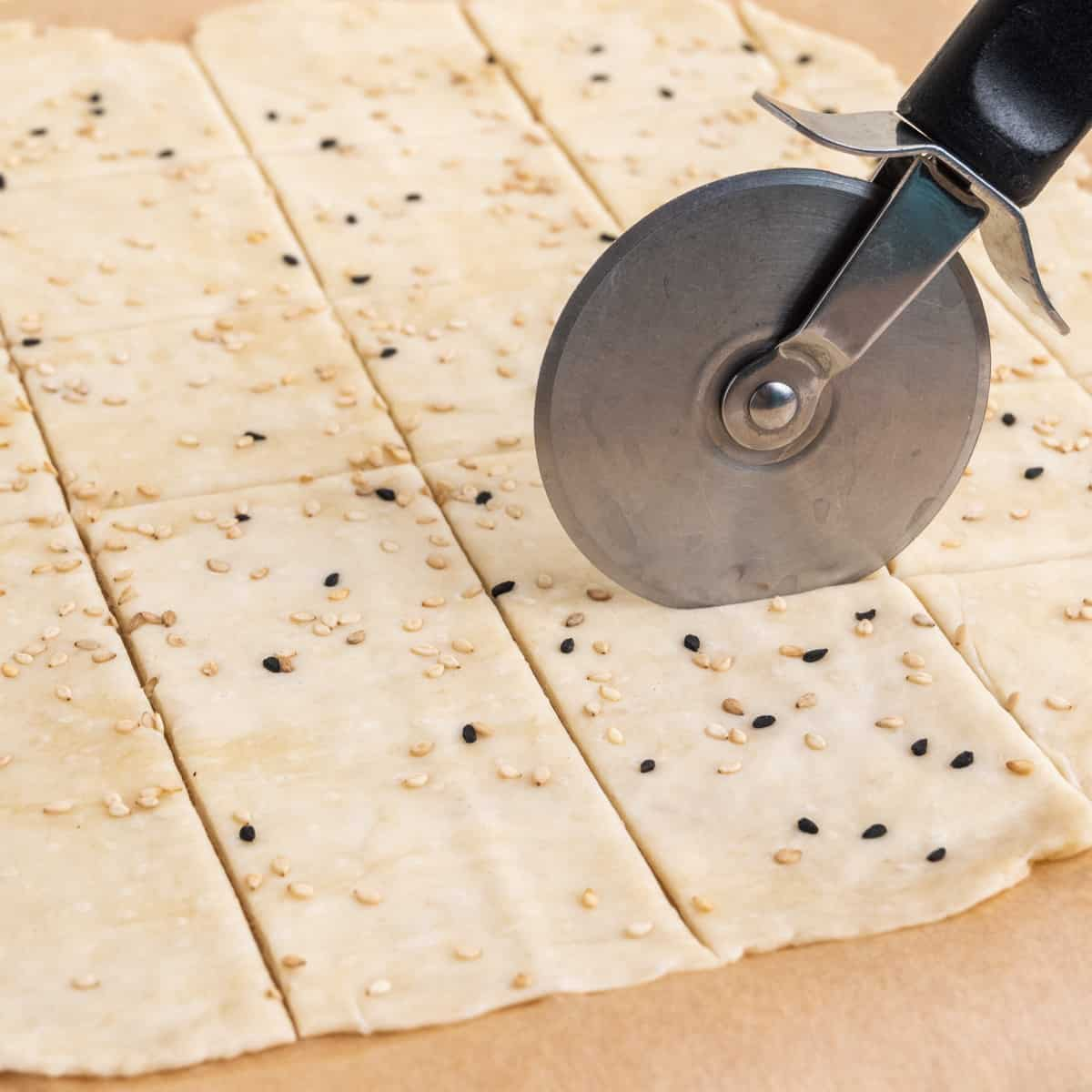 Cutting crackers into squares with a pizza roller.