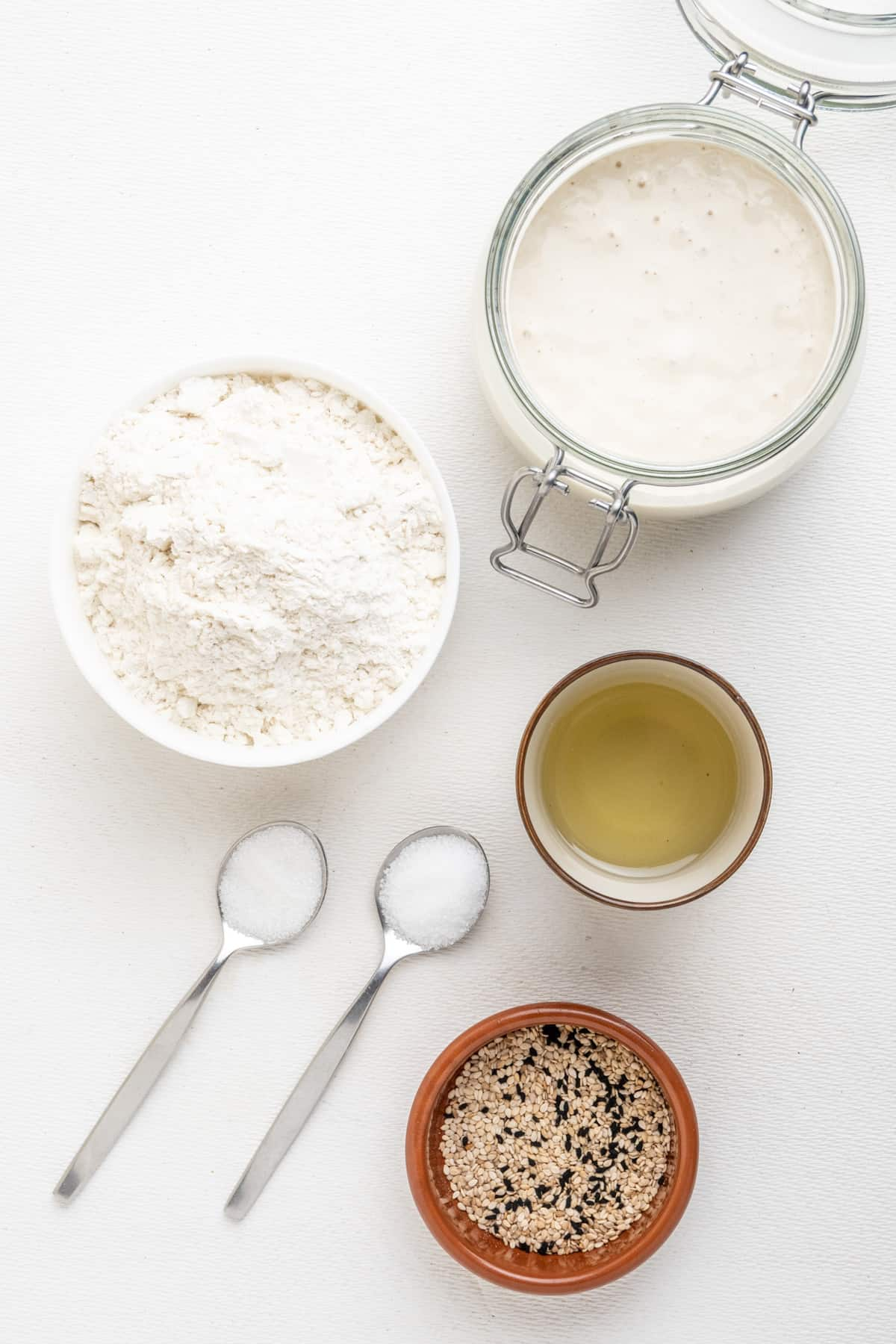 The ingredients on a white surface - sourdough discard, white flour, olive oil, salt, sugar and seeds.