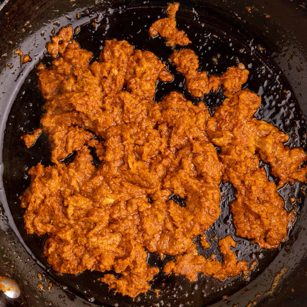 Red Curry paste in a frying pan. The oil is starting to separate from the paste.