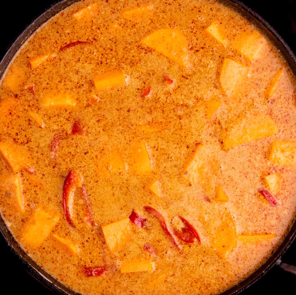 The orange red curry broth with sweet potato pieces and slices of red pepper simmering in a large frying pan.