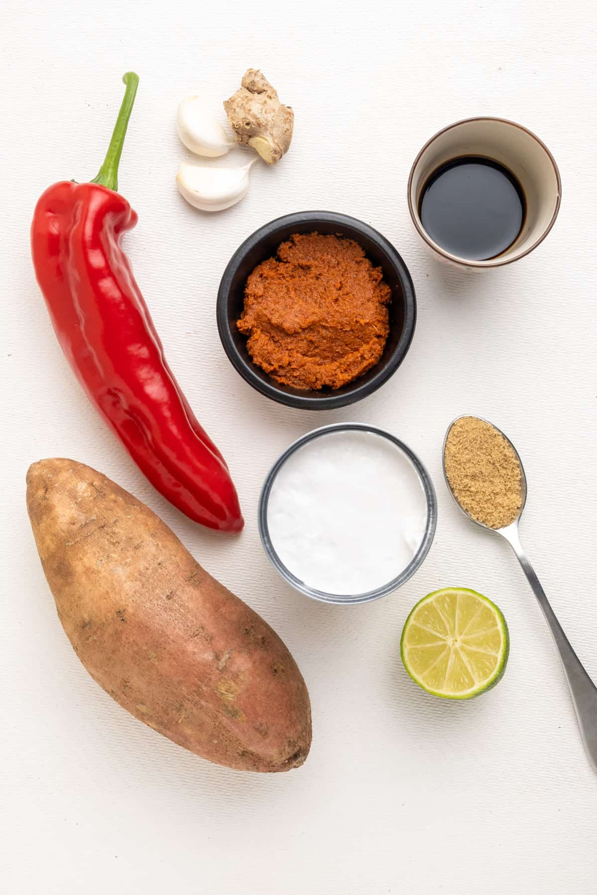 The most important ingredients for this recipe: A large sweet potato, a pointed red pepper, fresh garlic and ginger, red curry paste, coconut milk, soy sauce, brown sugar, and half a lime.