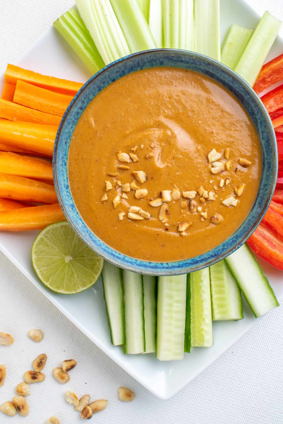 A bowl of thick dipping satay sauce surrounded by veggie sticks.
