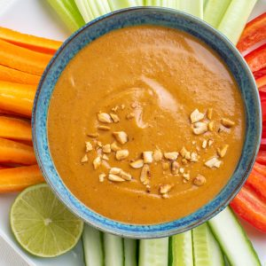 A bowl of thick vegan dipping satay sauce surrounded by veggie sticks.