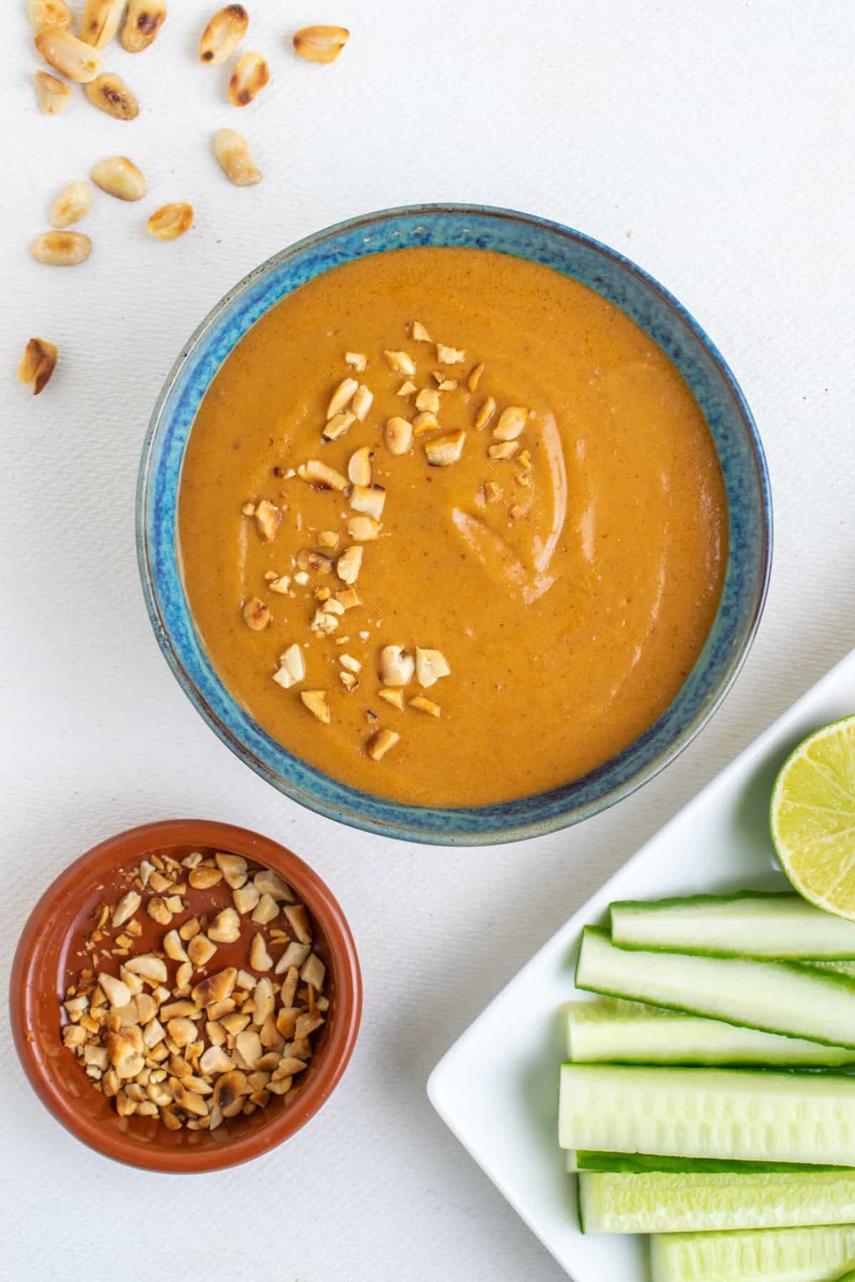 A blue pottery bowl full od Thai inspired peanut sauce, next to a dish of crushed peanuts.