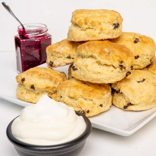 Scones served in a pile on a plate, with vegan whipped cream and raspberry jam.
