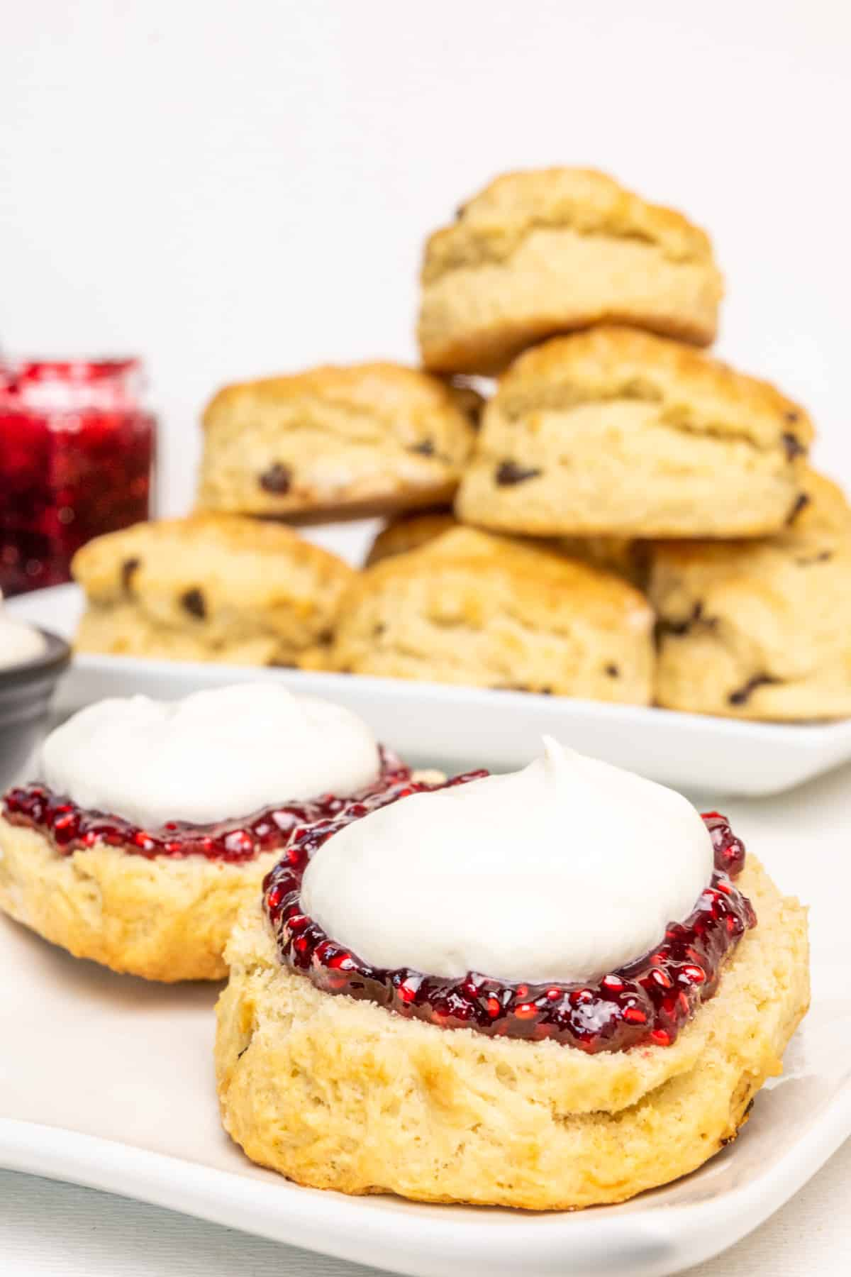A scone halved and topped with raspberry jam and a dollop of whipped cream, in front of a stack of scones on a plate.