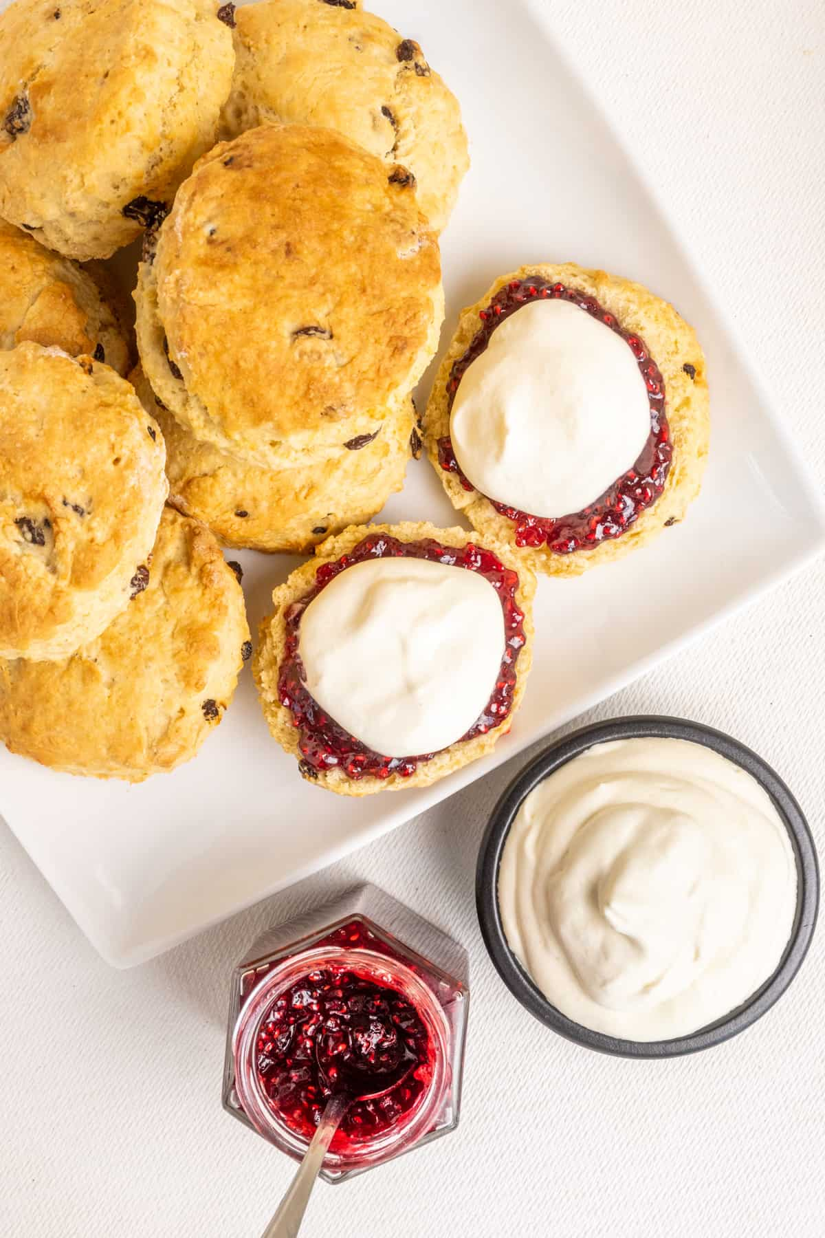 A completely vegan serving of scones, raspberry jam and whipped cream.