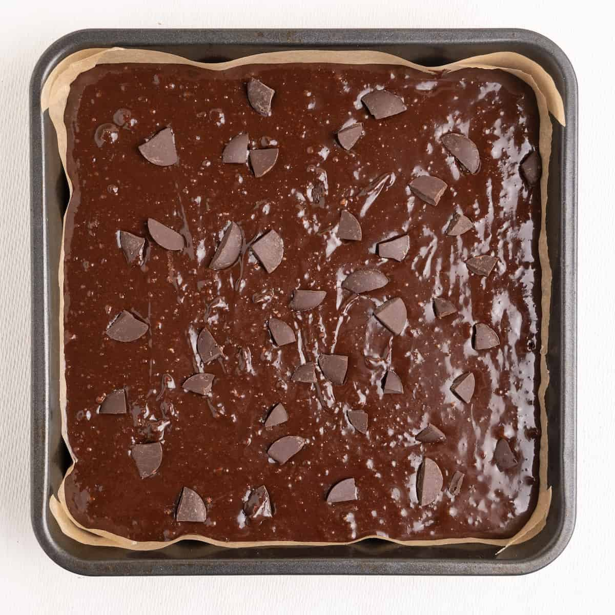 A square pan lined with baking paper containing unbaked brownie.