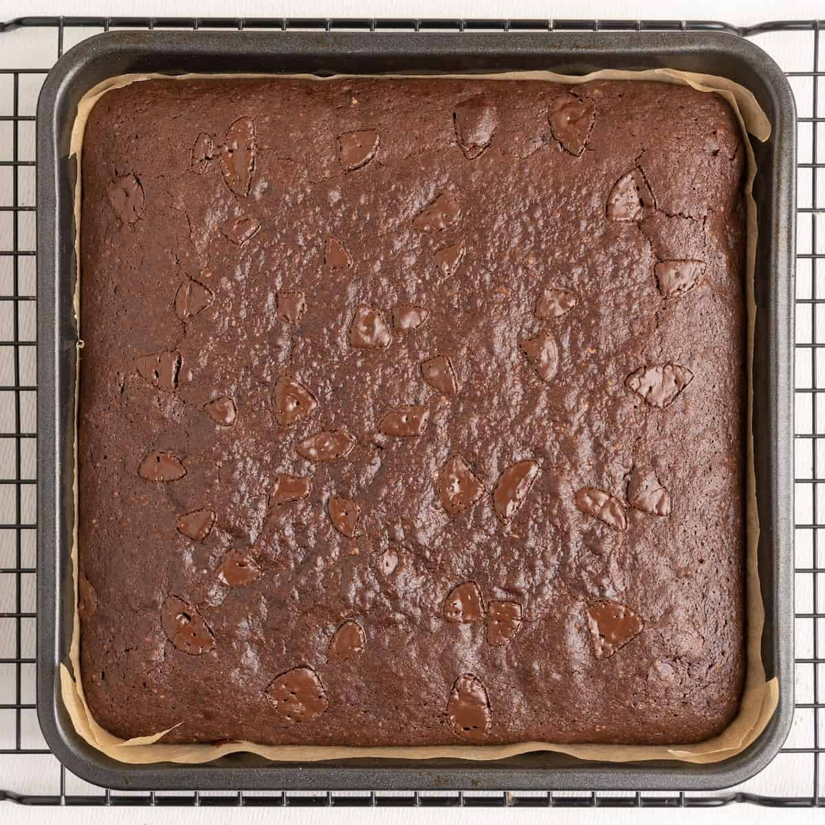 The baked brownie in a tin on a wire cooling rack.