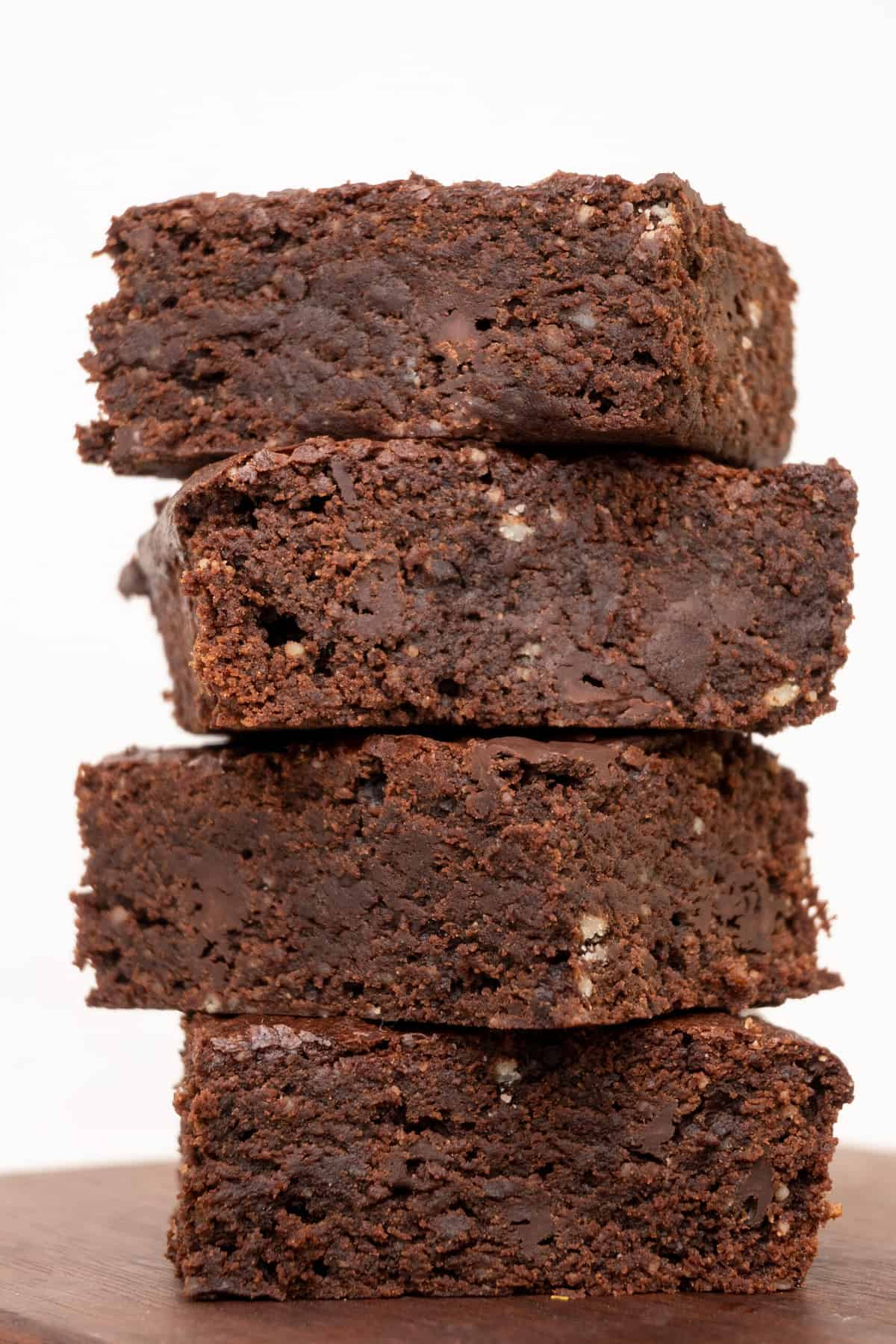 A stack of four vegan chocolate brownies seen from the side.