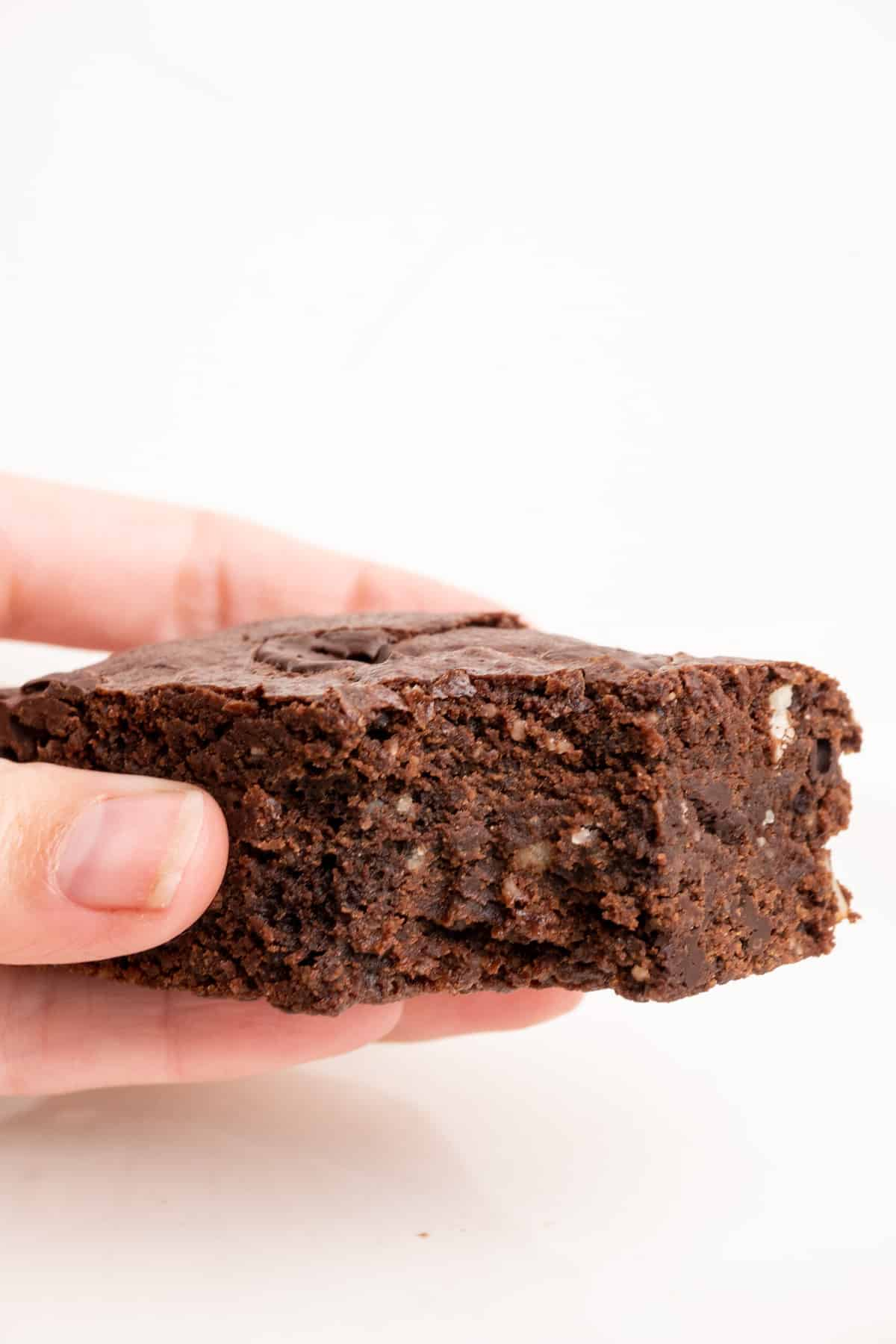 A hand holds a piece of brownie with a bite out of it.